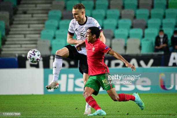 Germany's Amos Pieper is challenged by Portugal's Tiago Tomas during the 2021 UEFA European Under-21 Championship final football mat thech between...