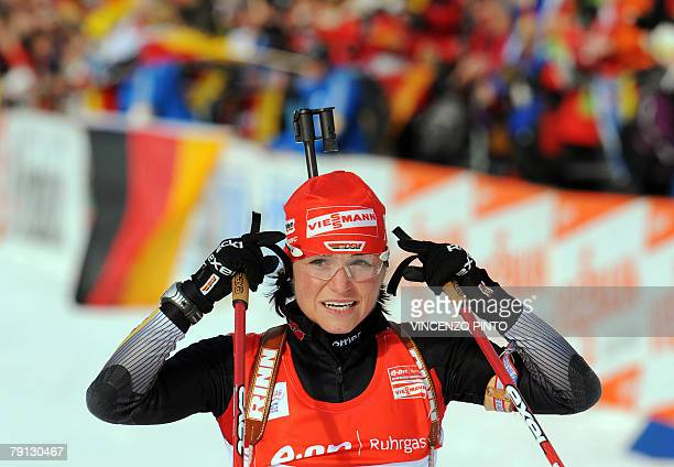 Germany's Andrea Henkel celebrates in the inish area after her victory in the Women's World Cup Biathlon's 125 km mass start 20 January 2008 in...