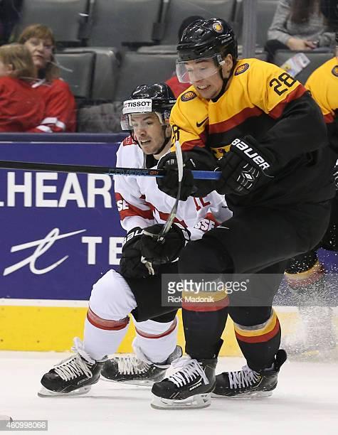 TORONTO JANUARY 3 Germany's Andreas Eder and Switzerland's Jason Fuchs battle for position 2015 IIHF World Junior Championship hockey between Germany...