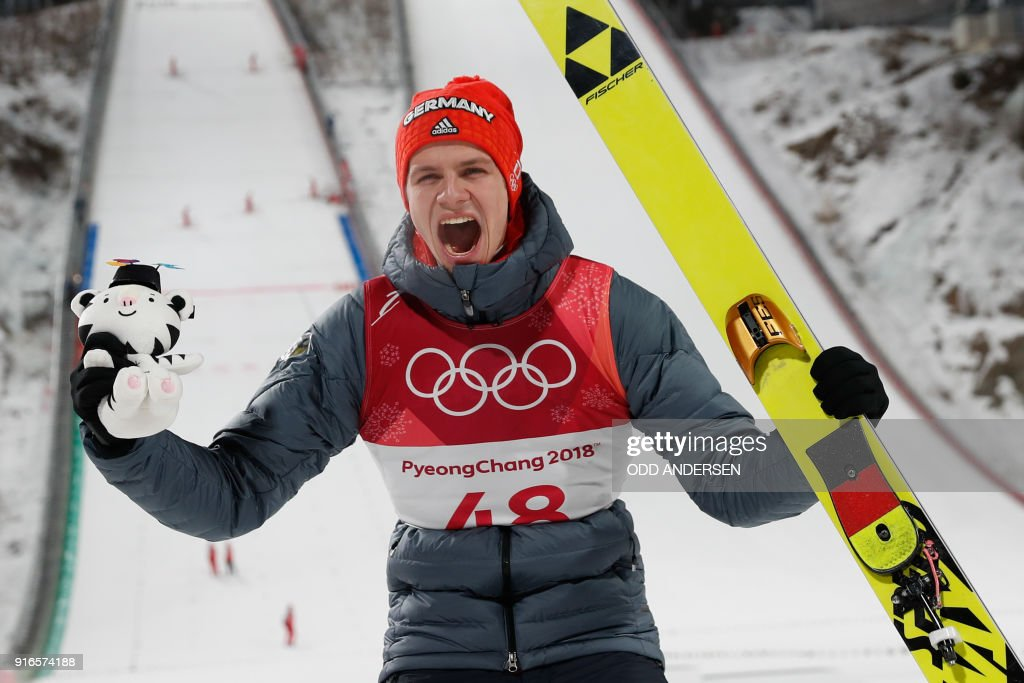TOPSHOT - Germany's Andreas Wellinger celebrates during the victory ceremony after winning the men's normal hill individual ski jumping event during the Pyeongchang 2018 Winter Olympic Games on February 10, 2018, in Pyeongchang. / AFP PHOTO / Odd ANDERSEN