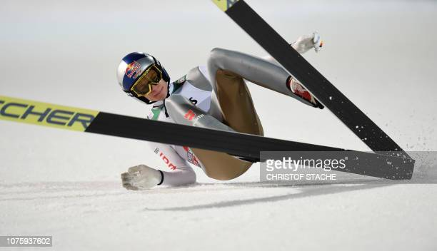 Germany's Andreas Wellinger falls after the finish line during his first competition jump of the first stage of the FourHills Ski Jumping tournament...