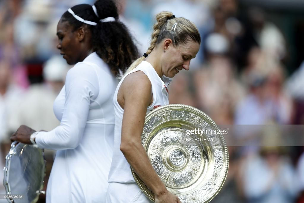 Germany's Angelique Kerber carries the winner's trophy, the Venus Rosewater Dish, after her women's singles final victory over US player Serena Williams on the twelfth day of the 2018 Wimbledon Championships at The All England Lawn Tennis Club in Wimbledon, southwest London, on July 14, 2018. - Kerber won the match 6-3, 6-3. (Photo by NIC BOTHMA / POOL / AFP) / RESTRICTED