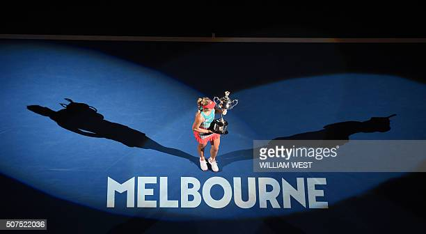 Germany's Angelique Kerber gestures as she holds The Daphne Akhurst Memorial Cup as she celebrates after victory her women's singles final match...