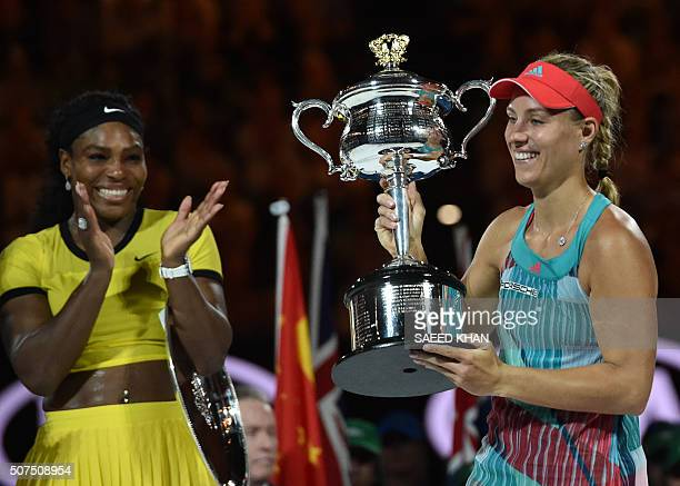 Germany's Angelique Kerber holds The Daphne Akhurst Memorial Cup as she celebrates after victory in her women's singles final match against Serena...