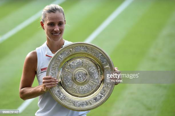 Germany's Angelique Kerber poses with the winner's trophy, the Venus Rosewater Dish, after her women's singles final victory over US player Serena...