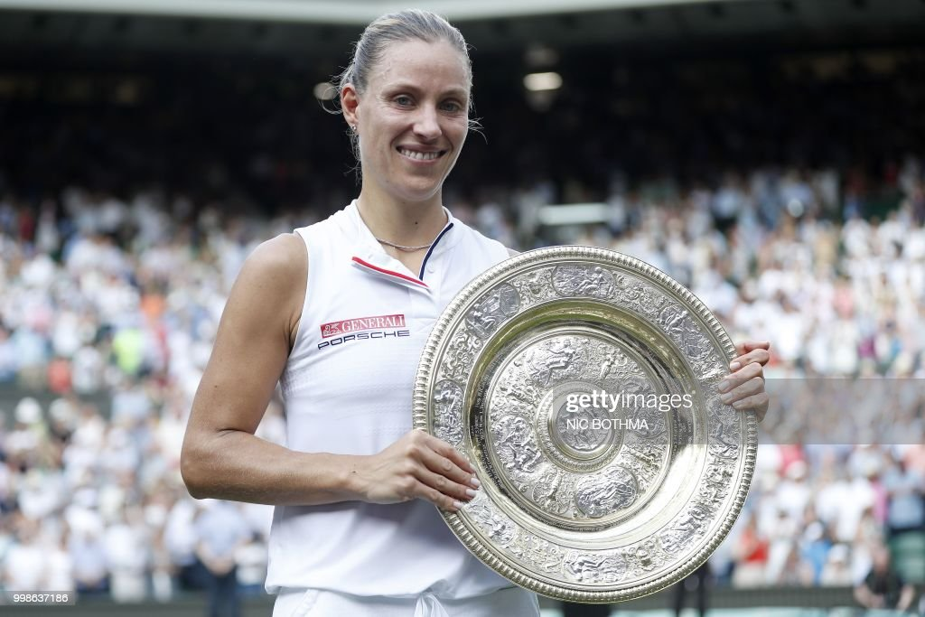 Germany's Angelique Kerber poses with the winner's trophy, the Venus Rosewater Dish, after her women's singles final victory over US player Serena Williams on the twelfth day of the 2018 Wimbledon Championships at The All England Lawn Tennis Club in Wimbledon, southwest London, on July 14, 2018. - Kerber won the match 6-3, 6-3. (Photo by NIC BOTHMA / POOL / AFP) / RESTRICTED