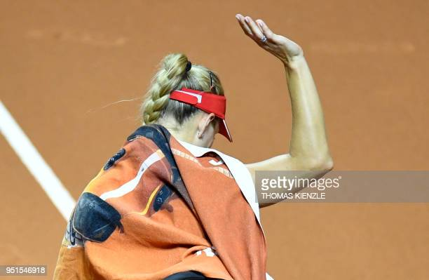 Germany's Angelique Kerber waves to the spectators after she was forced to give up due to an injury on her right leg her match against Estonia's...
