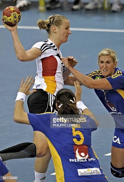 Germany's Ania Rosler is blocked by Sweden's Sara Holmgren and Matilda Boson during the preliminary round match between Germany and Sweden at the...
