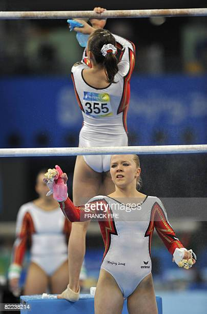 Germany's Anja Brinker and her teammate Joeline Mobius get ready to compete on the uneven bars during the women's qualification of the artistic...