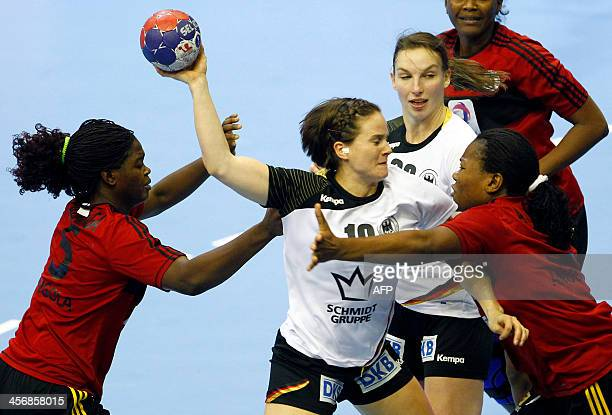 Germany's Anna Loerper and Angie Geschake vies with Angola's Bombo Madalena Calandula and Anastacia Solange Sibo during their Women's Handball World...