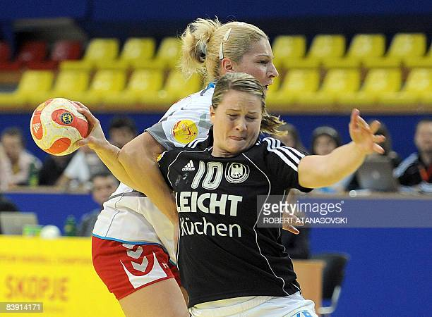 Germany's Anna Loerper fights for the ball with Serbia's Sanja Rajovic during their 8th Women's Handball European Championships match on December 4...