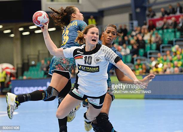 Germany's Anna Loerper vies with Brazil's Fernanda Silva and Ana Belo during the 2015 WomenÕs Handball World Championship group C match between...