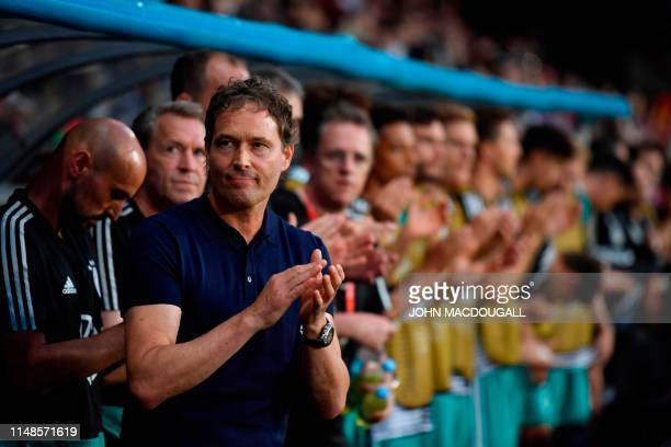 Germany's assistant coach Marcus Sorg applauds after listening to the national anthem prior to the Euro 2020 football qualification match between...