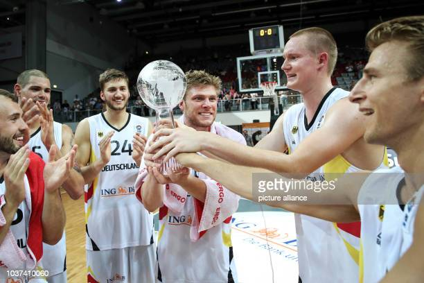 Germany's Bastian Doreth Maik Zirbes Maximiliian Kleber Lucca Staiger Robin Benzing and Heiko Schaffartzik cheer with the trophy after the Basketball...