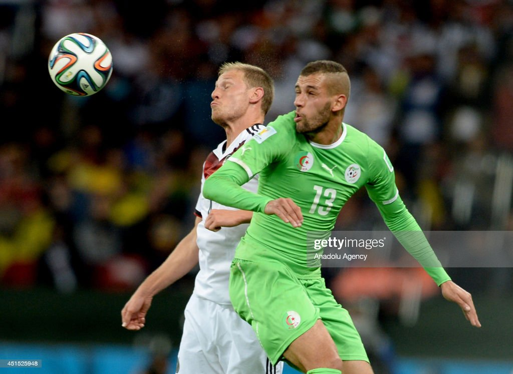 Germany's Benedikt Howedes vies for the ball Algeria's Islam Slimani (13) during the 2014 FIFA World Cup Brazil Round of 16 match between Germany and Algeria at Estadio Beira-Rio on June 30, 2014 in Porto Alegre, Brazil.