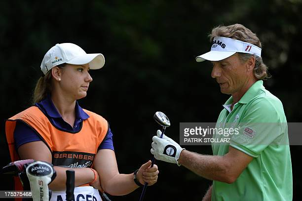 Germany´s Bernhard Langer hands a golf club to his daughter Christina as he competes at the second round of the Berenberg Bank Masters Cologne...