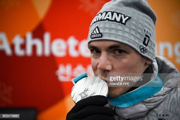 Germany's biathlon silver medallist Simon Schempp kisses his medal backstage at the Athletes' Lounge after the medal ceremonies at the Pyeongchang...