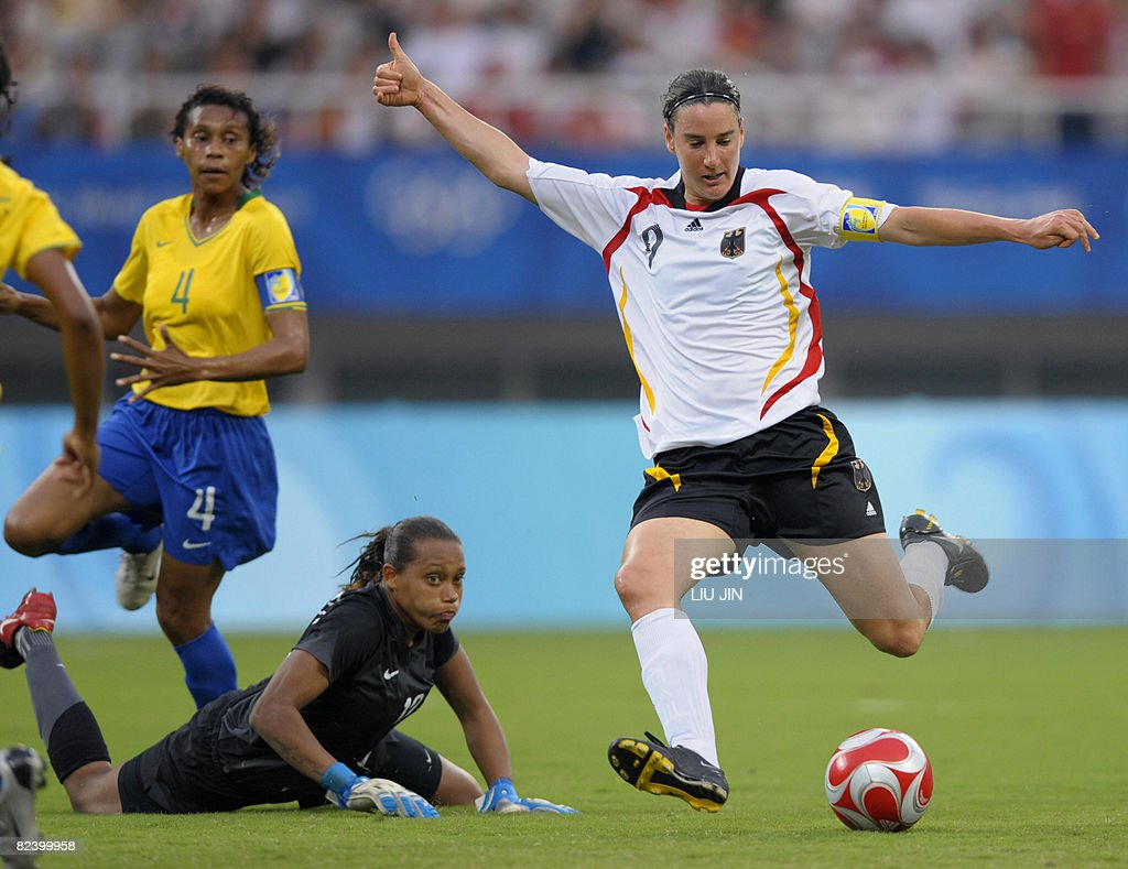 Germany's Birgit Prinz (R) shoots to score a goal against Brazil's goalkeeper Barbara (dowb) during their 2008 Beijing Olympic Games women's semi-final football match at the Shanghai Stadium on August 18, 2008. AFP PHOTO/LIU Jin