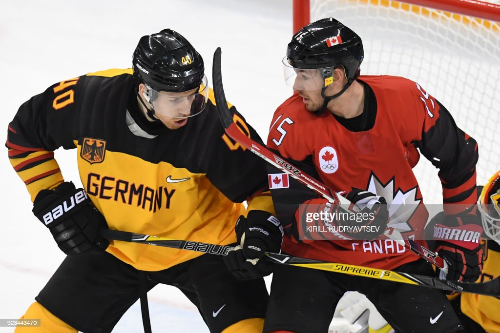TOPSHOT - Germany's Bjorn Krupp (L) and Canada's Brandon Kozun compete in the men's semi-final ice hockey match between Canada and Germany during the Pyeongchang 2018 Winter Olympic Games at the Gangneung Hockey Centre in Gangneung on February 23, 2018. / AFP PHOTO / Kirill KUDRYAVTSEV
