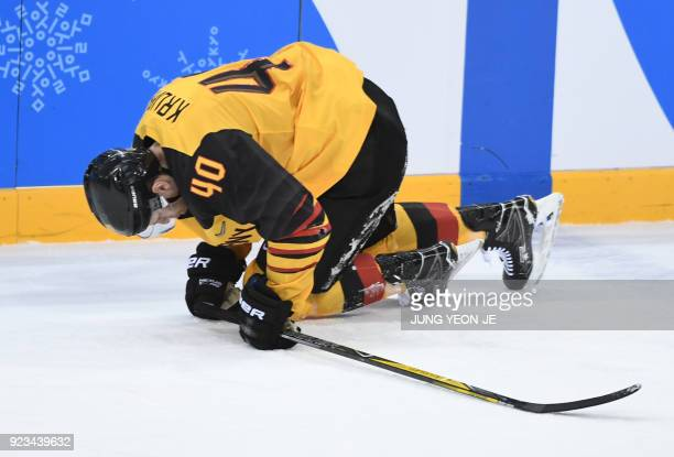 Germany's Bjorn Krupp falls to the ground after being hit with a high stick in the men's semifinal ice hockey match between Canada and Germany during...