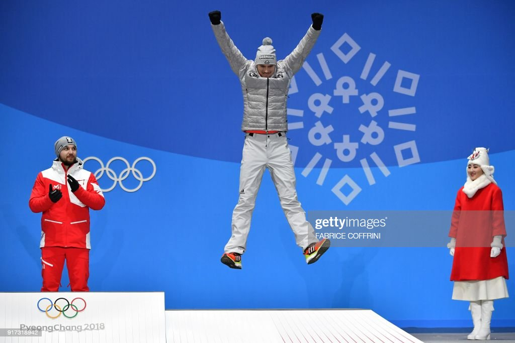 Germany's bronze medallist Johannes Ludwig jumps on the podium during the medal ceremony for the men's luge singles at the Pyeongchang Medals Plaza during the Pyeongchang 2018 Winter Olympic Games in Pyeongchang on February 12, 2018. / AFP PHOTO / Fabrice COFFRINI
