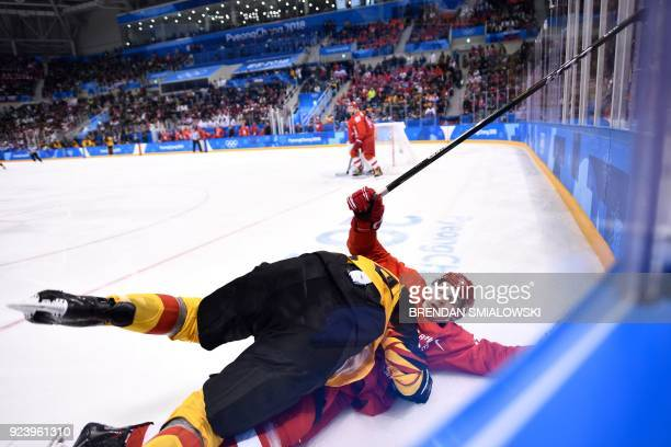 Germany's Brooks Macek and Russia's Bogdan Kiselevich lie on the ice after colliding in the men's gold medal ice hockey match between the Olympic...
