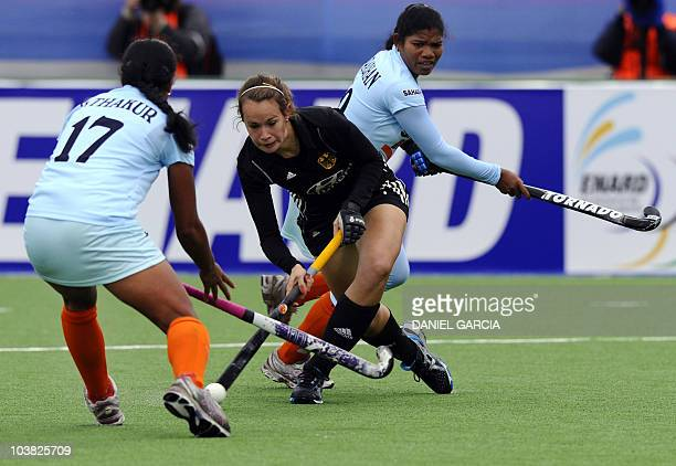 Germany's Celine Wilde drives the ball as India's Deepika Thakur and Subhadra Pradhan try to stop her during a field hockey Group A match of the...