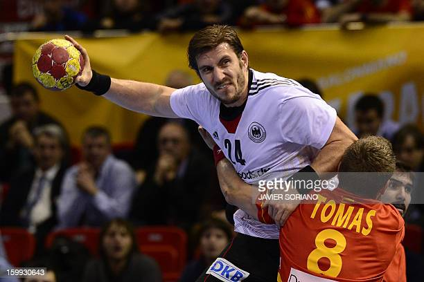 Germany's centre back Michael Haas vies with Spain's right wing Victor Tomas during the 23rd Men's Handball World Championships quarterfinal match...