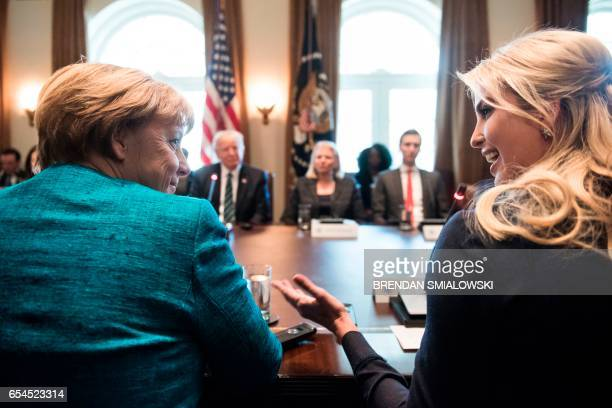 Germany's Chancellor Angela Merkel and Ivanka Trump talk before a meeting with US President Donald Trump and business leaders in the Cabinet Room of...