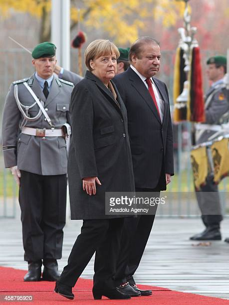 Germany's Chancellor Angela Merkel and Pakistan's Prime Minister Nawaz Sharif walk together as honor guards stand still in front of the Prime...