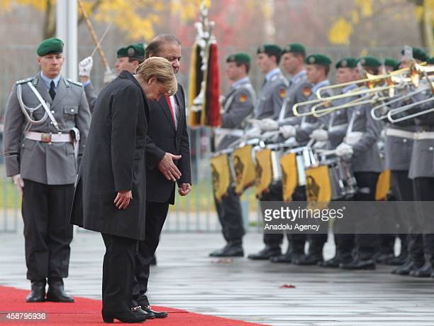 Germany's Chancellor Angela Merkel and Pakistan's Prime Minister Nawaz Sharif salute together as honor guards stand still in front of the Prime...