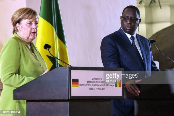 Germany's Chancellor Angela Merkel and Senegal's President Macky Sall give a joint press conference after their meeting on August 29 2018 in Dakar...