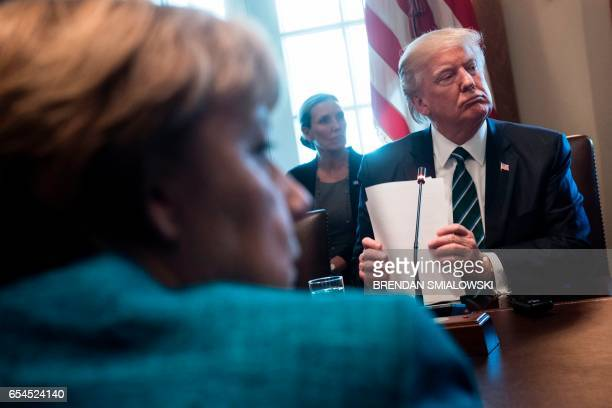 TOPSHOT Germany's Chancellor Angela Merkel and US President Donald Trump listen as participants introduce themselves before a meeting with Germans...