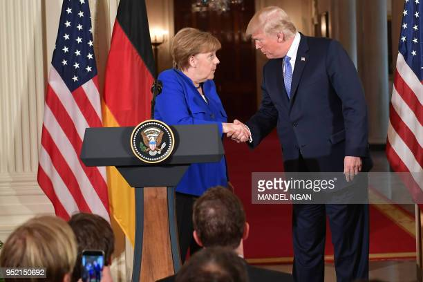 Germany's Chancellor Angela Merkel and US President Donald Trump shake hands during a joint press conference in the East Room of the White House on...