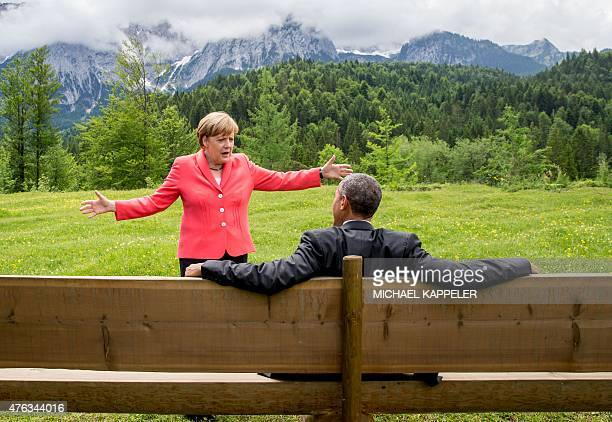Germany's Chancellor Angela Merkel gestures while chatting with US President Barack Obama sitting on a bench outside the Elmau Castle after a working...