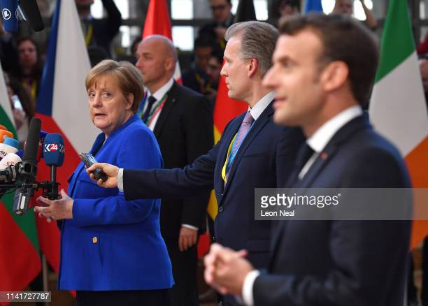 Germany's Chancellor Angela Merkel looks back at French President Emmanuel Macron as they speak to the media ahead of a European Council meeting on...