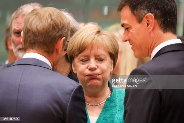 TOPSHOT Germany's Chancellor Angela Merkel reacts as she speaks with European Council President Donald Tusk and Spain's Prime Minister Pedro Sanchez...
