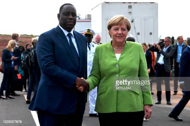 Germany's Chancellor Angela Merkel shakes hands with Senegal's President Macky Sall upon her arrival at Diass Airport on the outskirts of Dakar on...