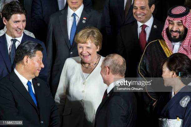 Germany's Chancellor Angela Merkel speaks to China's President Xi Jinping and Russia's President Vladimir Putin during a family photo session in...
