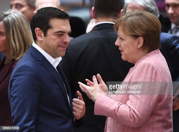 Germany's Chancellor Angela Merkel speaks to Greece's Prime Minister Alexis Tsipras as they attend a European leaders summit at the European Council...