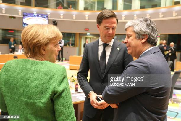 Germany's Chancellor Angela Merkel speaks with President of the Eurogroup Mario Centeno and Netherland's Prime minister Mark Rutte during a meeting...