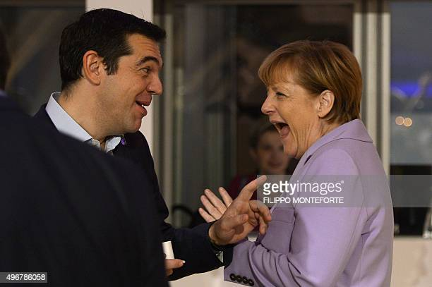 Germany's Chancellor Angela Merkel talks to Greece's Prime minister Alexis Tsipras as she arrives for a second working session of the European Union...