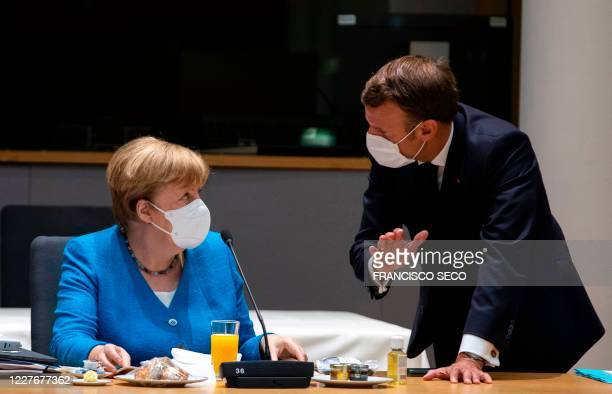 Germany's Chancellor Angela Merkel talks with France's President Emmanuel Macron prior the start of the EU summit at the European Council building in...