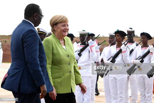 Germany's Chancellor Angela Merkel walks with Senegal's President Macky Sall while reviewing a guard of honour after her arrival at Diass Airport on...