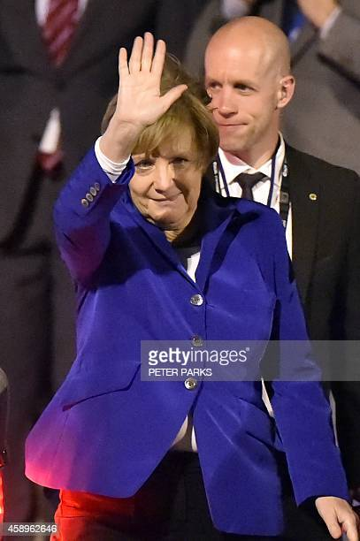 Germany's Chancellor Angela Merkel waves upon her arrival at the airport in Brisbane to take part in the G20 summit on November 14 2014 Australia...