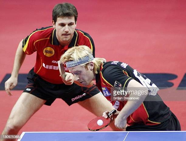 Germany's Christian Suess right and his partner Timo Boll serve during their men's double final match against Poland's Lucjan Blaszczyk and Croatia's...