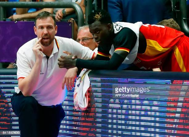 Germany's coach Chris Fleming speaks with point guard Dennis Schroder during their team's FIBA EuroBasket 2017 basketball championship match with...