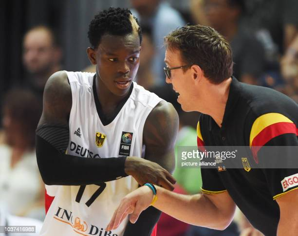 Germany's coach Chris Fleming talks to his player Dennis Schroeder during the men's international baskeball match Germany vs Czech Republic in...