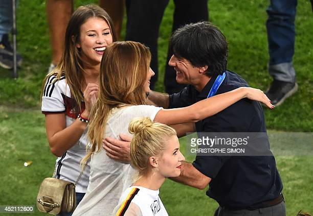 Germany's coach Joachim Loew hugs a partner of a German squad member after Germany won the 2014 FIFA World Cup final football match between Germany...