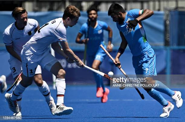 Germany's Constantin Staib and India's Manpreet Singh vie for the ball during the men's bronze medal match of the Tokyo 2020 Olympic Games field...